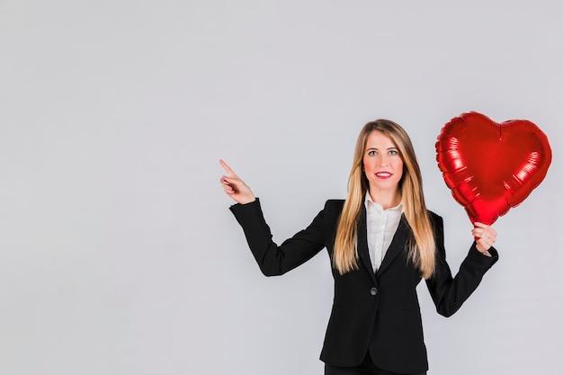 Portret van een blonde jonge onderneemster die rode folieballon houdt die ter beschikking haar vinger richt