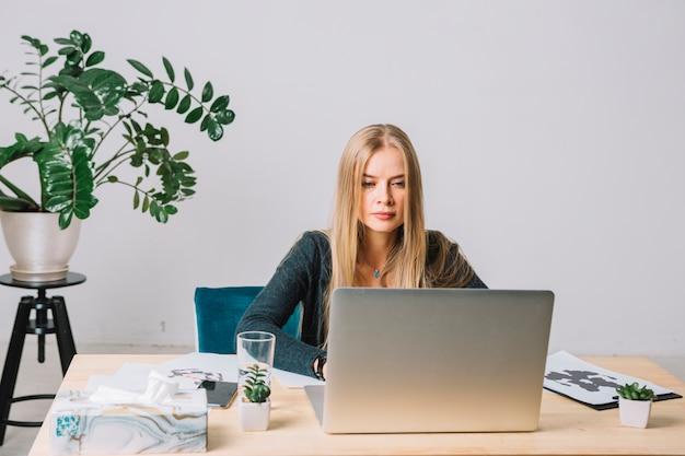 Portret van een blonde jonge psycholoog met behulp van laptop op tafel in het kantoor