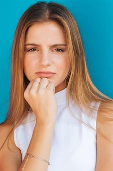 Portret van een blonde jonge vrouw die camera tegen blauwe achtergrond bekijkt