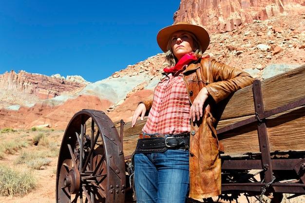 Portret van een blonde jonge vrouw die een cowboyhoed draagt