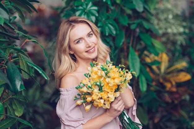 Portret van een blonde jonge vrouw die geel bloemboeket houdt