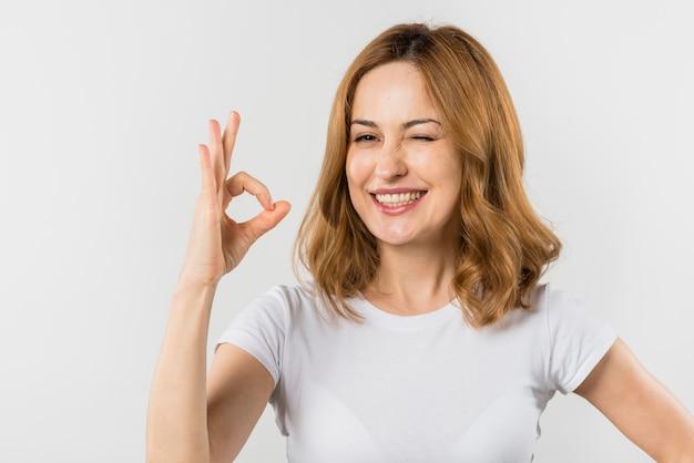Portret van een blonde jonge vrouw die ok teken maakt dat tegen witte achtergrond knipoogt