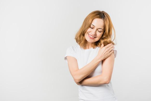 Portret van een blonde jonge vrouw die op witte achtergrond wordt geïsoleerd