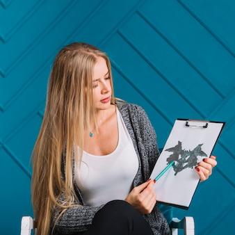 Portret van een blonde jonge vrouw die pen over de rorschach inkblot test richt tegen blauwe muur