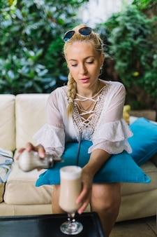 Portret van een blonde jonge vrouw die suiker in het latte macchiatoglas toevoegt
