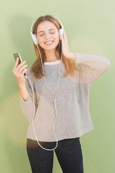 Portret van een blonde jonge vrouw die van de muziek op hoofdtelefoon geniet