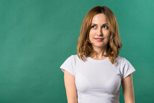 Portret van een blonde jonge vrouw die weg tegen groene achtergrond kijkt