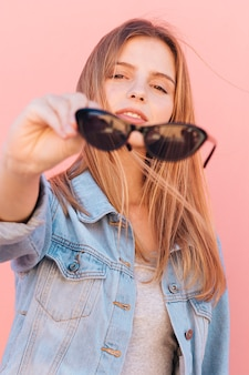 Portret van een blonde jonge vrouw die zwarte zonnebril houdt die ter beschikking camera bekijken