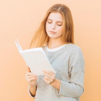 Portret van een blonde jonge vrouw leesboek tegen perzik kleur achtergrond