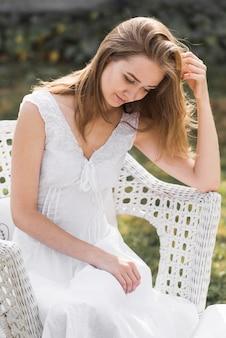 Portret van een blonde jonge vrouw zittend op een witte stoel in de open lucht