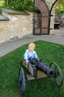 Portret van een blonde jongen in de buurt van een oud kanon
