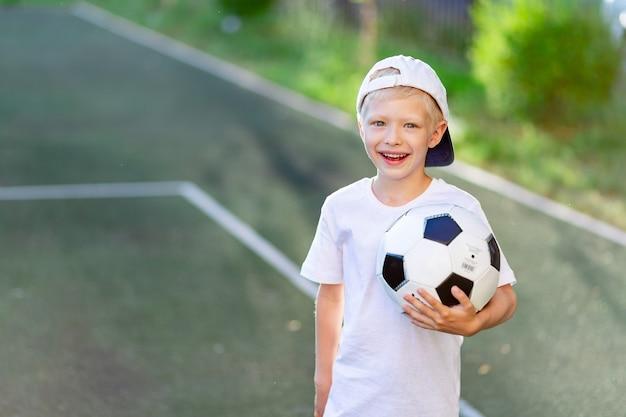Portret van een blonde jongen in een pet in een sportuniform met een voetbal in zijn handen op het voetbalveld