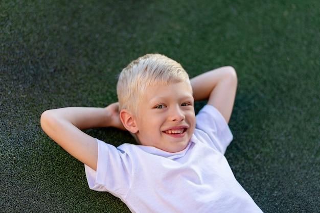 Portret van een blonde jongen in een sportuniform liggend op het voetbalveld