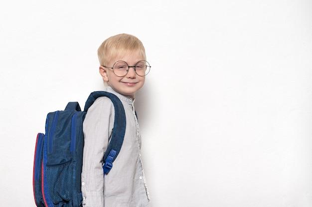 Portret van een blonde jongen in glazen en met een schoolrugzak op een witte achtergrond. school concept