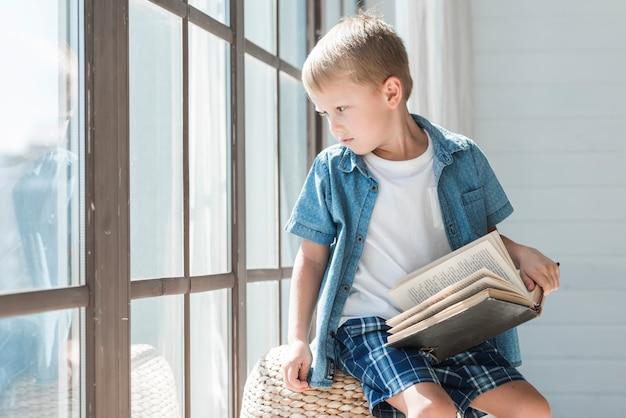 Portret van een blonde jongenszitting dichtbij het venster in zonlicht