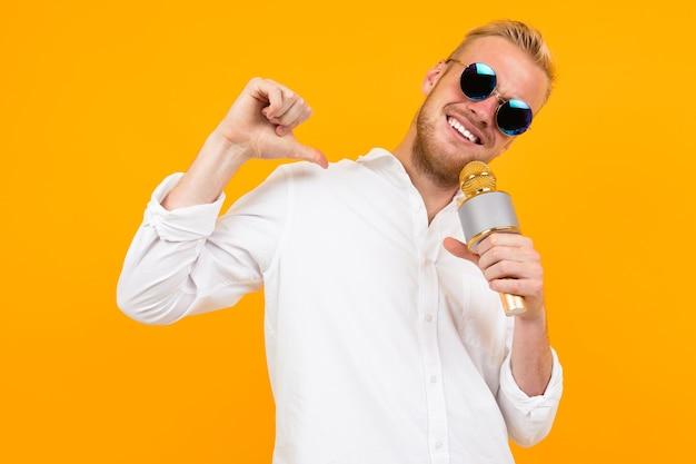 Portret van een blonde man in een wit overhemd die in een microfoon zingt