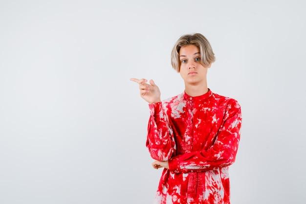 Portret van een blonde tienerman die naar links wijst in een te groot shirt en er ongezellig uitziet
