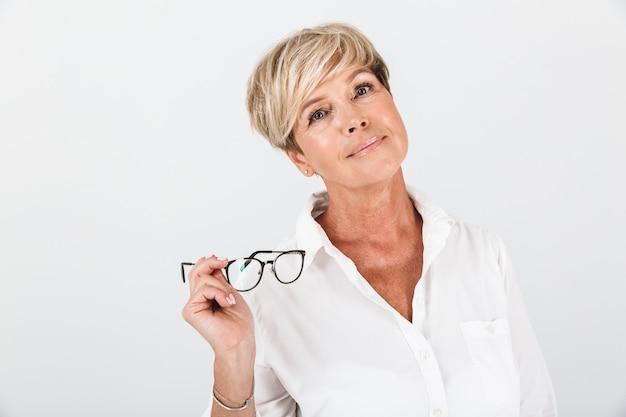 Portret van een blonde volwassen vrouw die een bril vasthoudt en naar een camera kijkt die over een witte muur in de studio wordt geïsoleerd