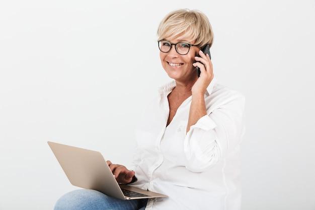 Portret van een blonde volwassen vrouw met een bril die op een smartphone praat terwijl ze zit met een laptopcomputer die over een witte muur wordt geïsoleerd