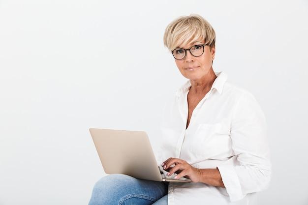 Portret van een blonde volwassen vrouw met een bril die zit met een laptopcomputer die over een witte muur in de studio wordt geïsoleerd