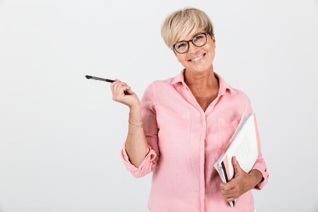 Portret van een blonde volwassen vrouw met een bril met studerende boeken en een pen geïsoleerd over een witte muur in de studio