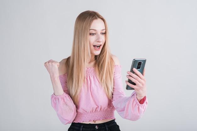 Portret van een blonde vrouw die een smartphone vasthoudt en het gebaar van de winnaar laat zien