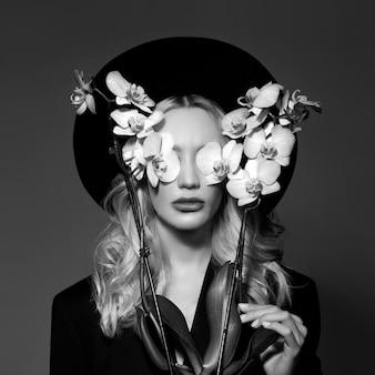Portret van een blonde vrouw in een grote ronde zwarte hoed, een orchideebloem in haar handen