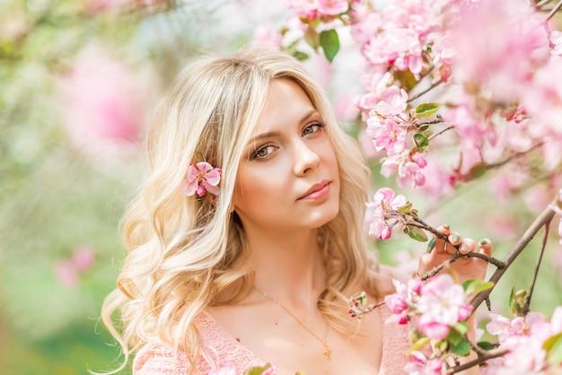 Portret van een blonde vrouw in roze bloemen. lente tuin