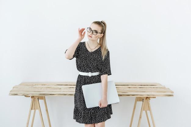Portret van een blonde vrouw met een bril en een jurk met een laptop die naar de voorkant kijkt