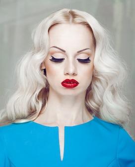 Portret van een blonde vrouw met gesloten ogen, met avondsamenstelling en rode lippen