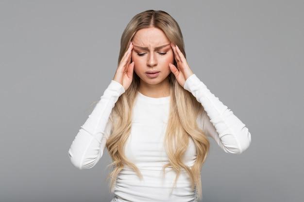Portret van een blonde vrouw met hoofdpijn