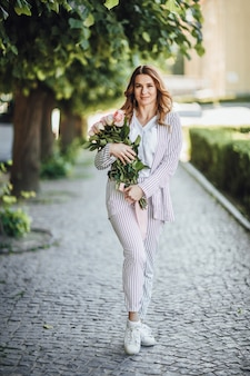 Portret van een blonde vrouw van middelbare leeftijd in vrijetijdskleding in de straat met een boeket rozen