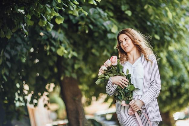 Portret van een blonde vrouw van middelbare leeftijd in vrijetijdskleding op straat met een boeket rozen
