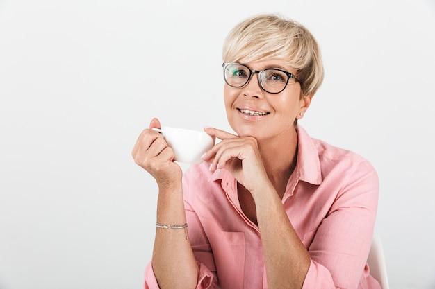 Portret van een blonde vrouw van middelbare leeftijd met een bril die lacht en een koffiekopje vasthoudt, geïsoleerd over een witte muur