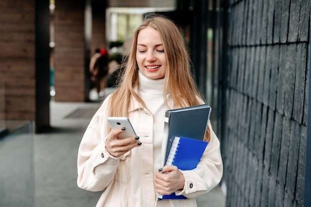 Portret van een blonde vrouwelijke student die glimlacht en mobiele telefoon gebruikt, sms't, typt en een bericht leest tegen de achtergrond van een universiteitsgebouw