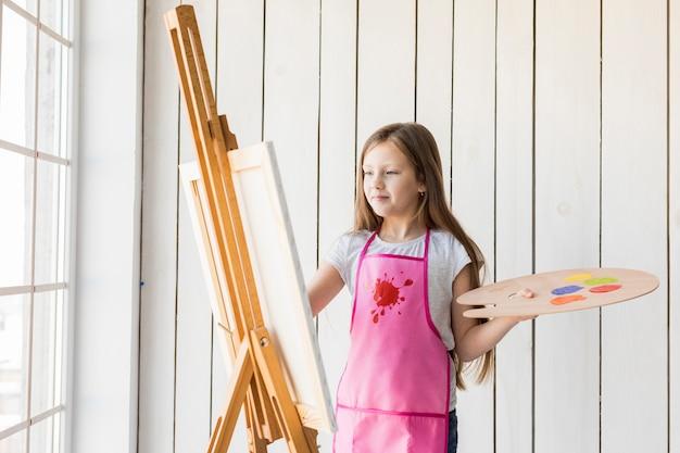 Portret van een blondemeisje die het houten palet schilderen op de schildersezel houden