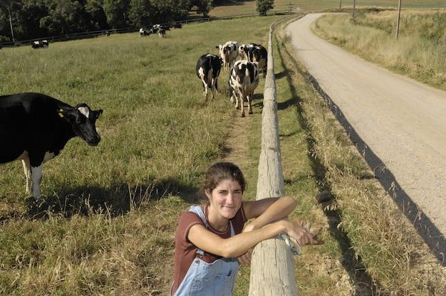 Portret van een boer met haar koeien in het veld