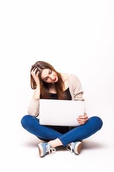 Portret van een boos meisje gekleed in tank-top met laptop zittend op de vloer over wit