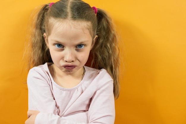 Portret van een boos meisje op een gele achtergrond, emoties bij kinderen.