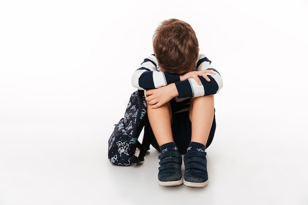 Portret van een boos verdrietig klein kind met rugzak
