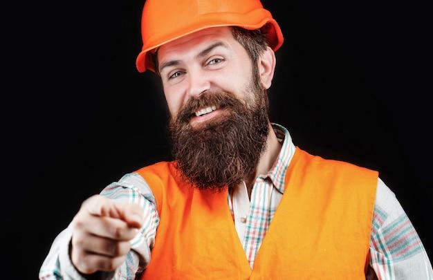 Portret van een bouwer die lacht. bebaarde man werknemer met baard in het bouwen van helm of harde hoed. mensenbouwers, industrie. bouwer in helm, voorman of reparateur in de helm