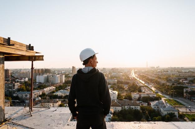 Portret van een bouwer in uniform op het dak van een nieuw wit gebouw buitenshuis