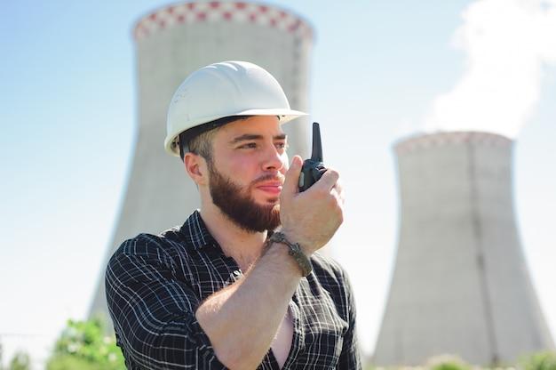 Portret van een bouwer-ingenieur met een radio in zijn hand.