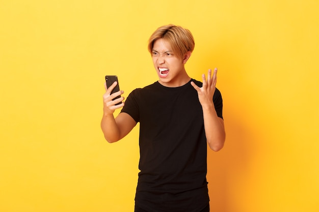 Portret van een boze en pissige aziatische man die boos kijkt naar het smartphonescherm, ruzie heeft tijdens videogesprek, staande gele muur