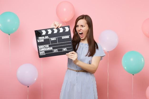 Portret van een boze geïrriteerde vrouw in blauwe jurk die schreeuwt met klassieke zwarte film die filmklapper maakt op roze achtergrond met kleurrijke luchtballonnen. verjaardagsfeestje, oprechte emoties van mensen.
