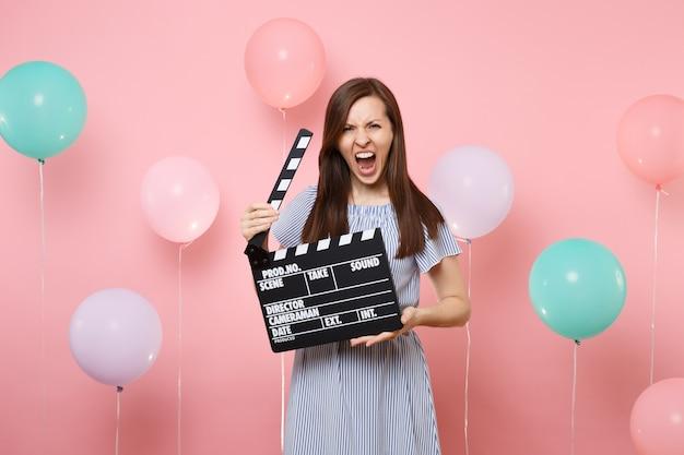Portret van een boze jonge vrouw die een blauwe jurk draagt die schreeuwt met klassieke zwarte film die filmklapper maakt op een roze achtergrond met kleurrijke luchtballonnen. verjaardagsfeestje, oprechte emoties van mensen.