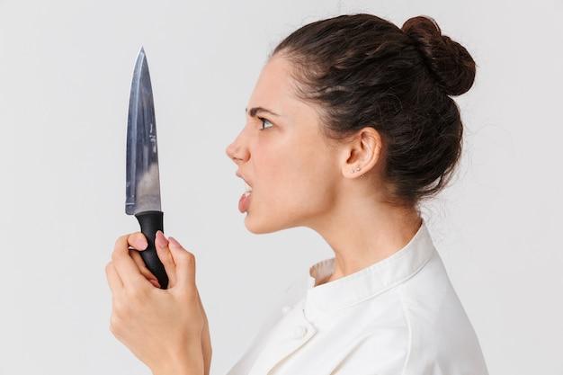 Portret van een boze jonge vrouw met keukengerei