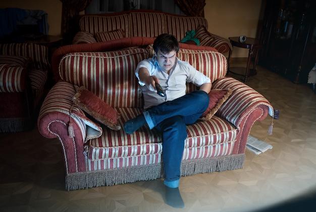 Portret van een boze man die van tv-kanaal wisselt terwijl hij op de bank zit