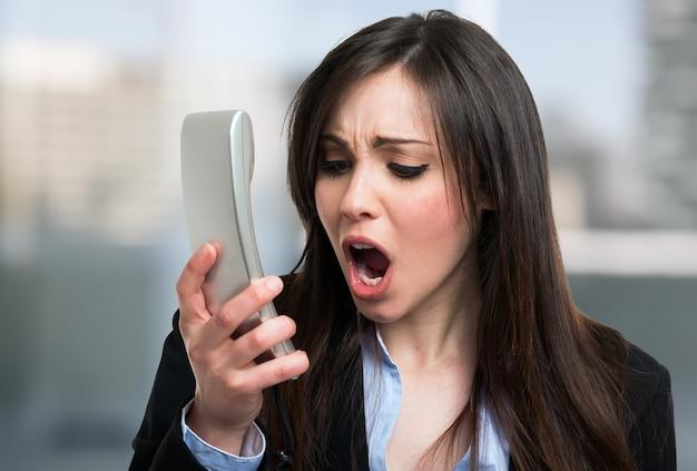 Portret van een boze onderneemster die bij telefoon schreeuwt