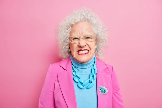 Portret van een boze senior vrouw met krullend haar squint gezicht en ziet er ongelukkig uit, drukt negatieve emoties uit en draagt een elegant kostuum met ketting en broche rode lippenstift transparante bril